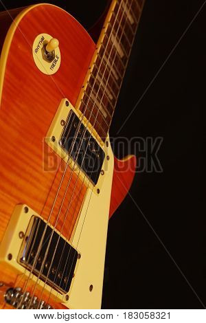 Vintage electric jazz guitar closeup on the black background. Shallow depth of field.