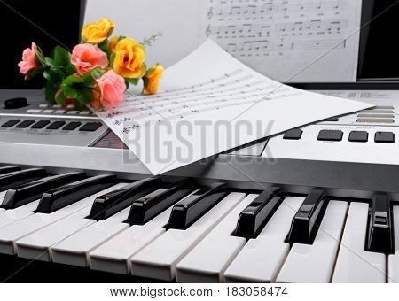 closeup fragment of electronic synthesizer keyboard with flowers and music notes sheets. selective focus