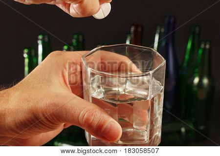 Hand with an effervescent pill from hangover over a glass of water on a dark background.