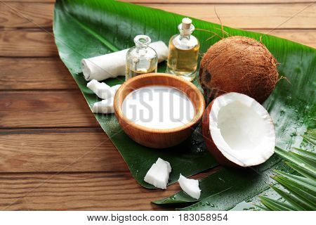 Spa composition with coconut and palm leaf on wooden background