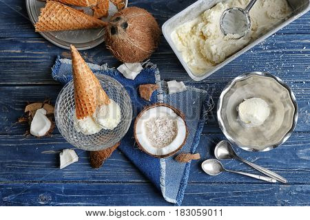 Composition of dishware with ice cream and desiccated coconut on wooden background
