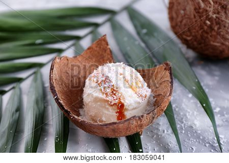 Plate with composition of ice cream ball in coconut shell, closeup