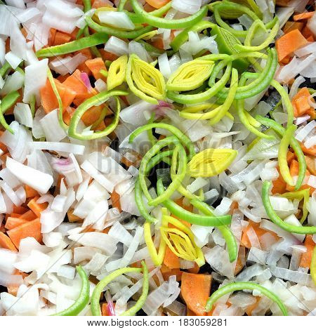 Healthy eating. Still life with sliced carrots, onion, leek before frying as background top view close up