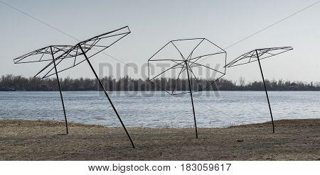 Beach umbrellas stationary near the pond in the off season
