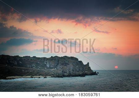 Landscape. Sea coast at sunset and sun on the horizon