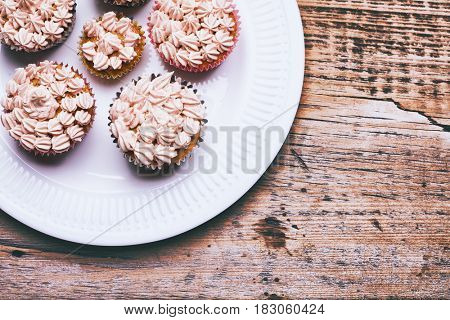 Tasty cupcakes on a old wooden table, vanilla cupcakes with pink and white cream, selective focus, close-up
