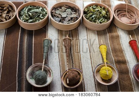 Colorful threds on wooden spindles and bowls with natural colorants