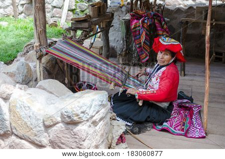 Old woman weaves at the traditional Peruvian loom outdoors