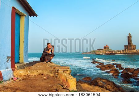 Traveling in India. Man photographing sunset off the coast of Kanyakumari. Tamil Nadu state South India 21.03.2017.