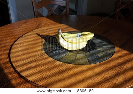 HARBOR SPRINGS, MICHIGAN / UNITED STATES - NOVEMBER 22, 2016: A bunch of bananas sits in the center of a round Lazy Susan dining table.