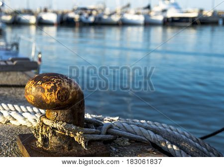 Old Rusty Iron Mooring Bollard and Nautical Ropes