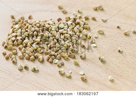 A handful of buckwheat scattered on wooden cutting Board