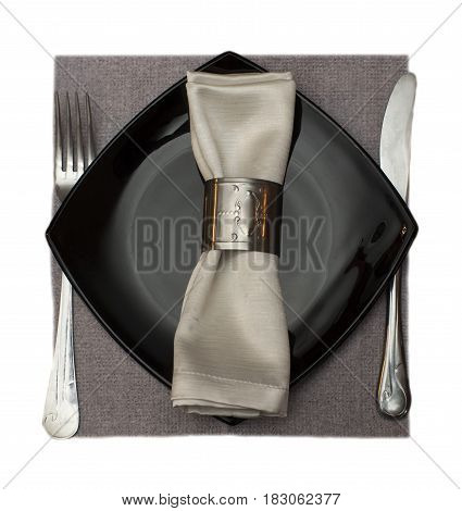 Fork knife and napkin served on a black plate