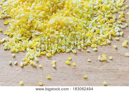 Crushed Golden corn grits scattered on a wooden Board fodder
