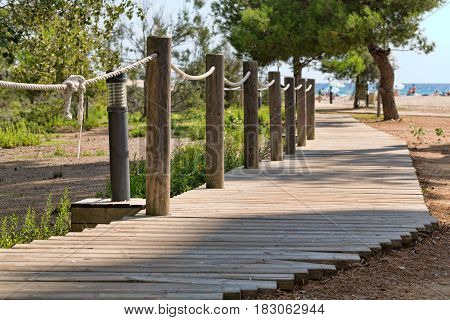 paved trail with wooden rope handrail leading to beautiful ocean beach