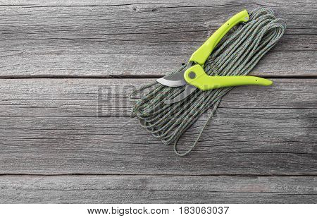 Secateur on wooden boards and a hank of garden rope.