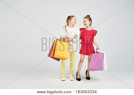 Young ladies are standing are the studio and holding shoppers bags. Girls are Imitating adult women. Shopping, purchases, buy concept