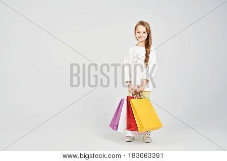 Blonde girl is holding variety of shoppers bags. She is smiling at the camera. Shopping, purchases, buy, sale concept
