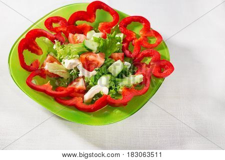 Fresh vegetables on a white background. Sweet pepper a cucumber and green lettuce leaves lie on a white board. Red pepper is cut with rings on pieces