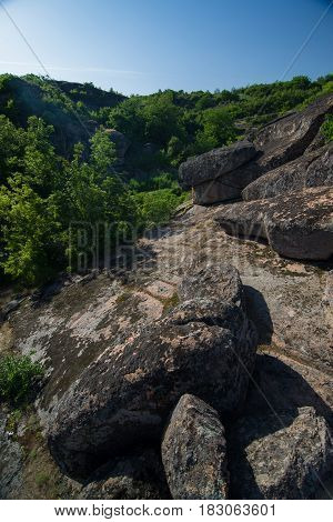 Valley of the granite ridge with huge stone boulders and forest on the slopes