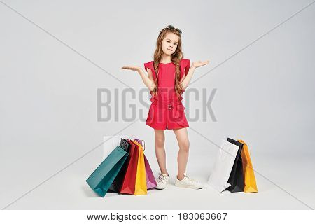 Young girls is standing in variety of colorful shoppers bags. Little girl is posing to the camera. The image is take at the studio. Shopping, purchase, buy concept