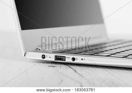 Detail on HDMI connector card slot Ultra-thin notebook. The silver notebook on the desk the open notebook lies on a wooden background.