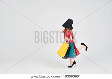 Young lady in red dress is waking. She has oversized shoes and hat. Little girl is holding shoppers bags. Girl is Imitating adult women