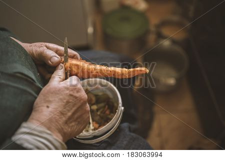 Old Grandmother Cutting Cuts Off Peel Carrots, Close