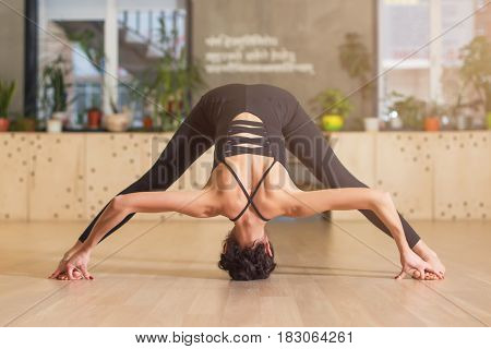 Young athletic girl doing stretching yoga exercises. Standing with barefoot legs apart and hands and head touching the floor.