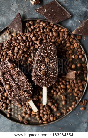 Chocolate ice cream on a stick on a gray background. Chocolate dessert. Ice. Coffee beans and chocolate.