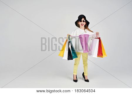 Little girl is wearing oversized hat and shoes. She is opening a purple shoppers bag. Girl has a surprised emotion on her face. Shopping, purchases, buy, sale concept