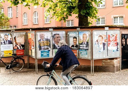 STRASBOURG FRANCE - APR 23 2017: Cyclist in front of French presidential campaign posters looking at them during first election day in France