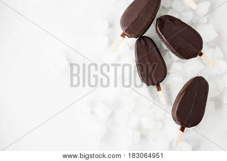 Chocolate ice cream on a stick on ice on a light background.