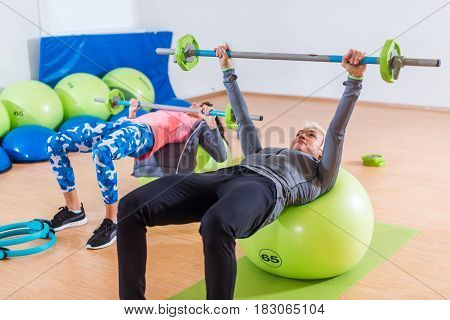 Fit female sportswomen doing barbell chest press exercise lying on stability ball in gym.