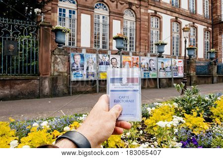 STRASBOURG FRANCE - APR 23 2017: Man holding Carte Electorale - voter's card French voter registration card in front of official campaign posters for all eleven candidates for the 2017 French presidential elections outside pooling station