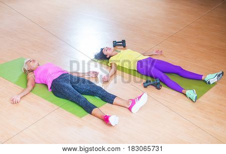 Two exhausted female athletes lying on floor on mats recovering after intensive workout. Women wearing bright sportswear resting after training in a gym.