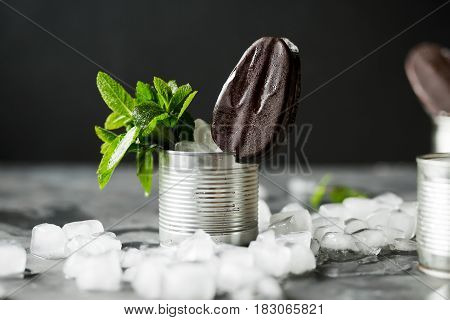 Chocolate ice cream on a stick in an iron jar on a black background. Chocolate dessert. Ice. Fresh mint