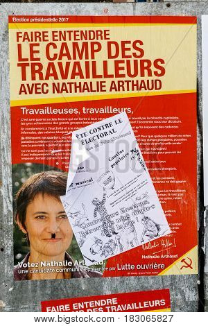 STRASBOURG FRANCE - APR 23 2017: Official campaign posters of Nathalie Arthaud political party leader of Lutte ouvriere (LO) vandalized on the first round of 2017 French presidential election