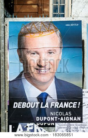 STRASBOURG FRANCE - APR 26 2017: Official campaign posters of Nicolas Dupont-Aignan political party leader of Debout la France (DLF) vandalized on the first round of 2017 French presidential election