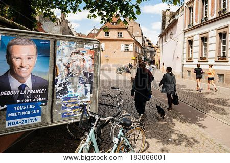 STRASBOURG FRANCE - APR 26 2017: Street view of multiple vandalized elections posters on the first round of 2017 French presidential election