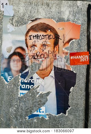 STRASBOURG FRANCE - APR 26 2017: Official campaign posters of Emmanuel Macron political party leader of En marche ! (EM !) vandalized on the first round of 2017 French presidential election