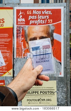 STRASBOURG FRANCE - APR 23 2017: French voter registration card held by male hand in front of official campaign poster of Philippe Poutou candidate for the 2017 French presidential elections posted outside a polling station