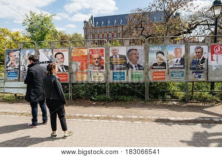 STRASBOURG FRANCE - APR 23 2017: People looking at the official campaign posters for all eleven candidates for the 2017 French presidential elections posted outside a polling station
