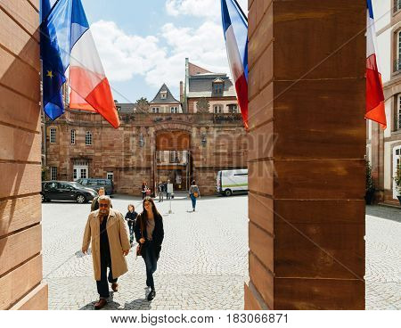 STRASBOURG FRANCE - APR 23 2017: Front view of people walking toward Voting station Bureau de Vote decorated with French Flags for the 2017 French presidential elections posted