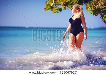 Young Plus Size Woman In Swimwear Enjoying Vacation In Water Splash On The Beach
