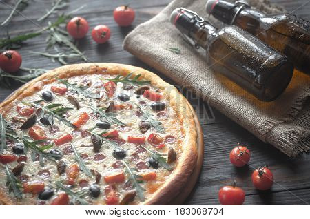 Cooked pizza with arugula on the wooden table