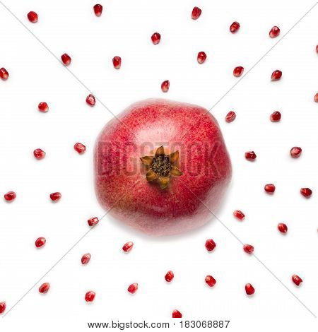 Ripe pomegranate in the center and fruit pomegranate seeds scattered in a chaotic manner, isolated on white background. Food background.