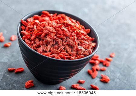 Goji berries in bowl on dark background closeup