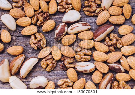 Concept - Nuts mix on old rustic wooden table. Almonds Brazil nuts and walnuts background. Healthy edible seeds food ingredient on the table. Top view. Directly above.