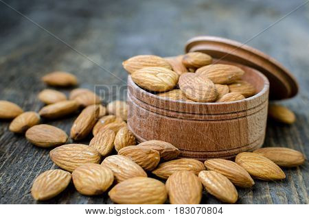 Tasty almonds nuts in wooden bowl on the old background. Healthy edible seeds food ingredient on the table.